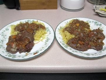 Two plates of steak pizzaiola with angel hair pasta in butter sauce
